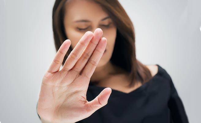 片手で断る女性