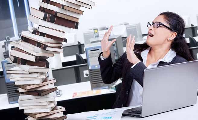 デスクの上で崩れかかる資料を押さえようとする女性