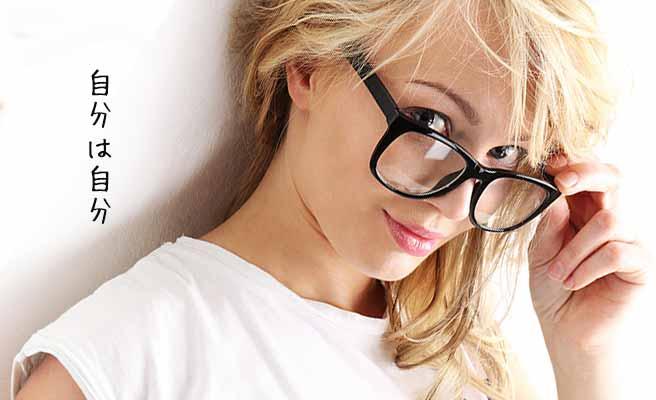 眼鏡を押さえながら微笑する女性