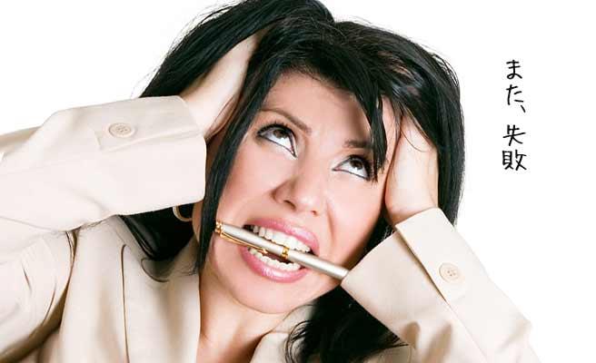 頭を搔きむしりペンをかじる女性