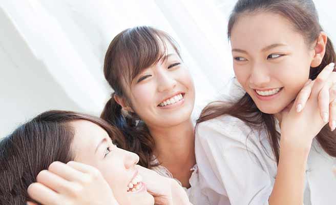 笑顔を向け合って会話する女性達