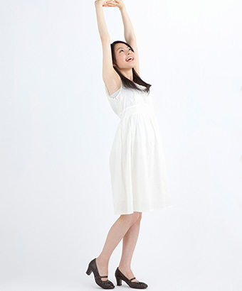 手を上げて背筋を伸ばす女性