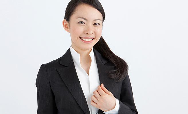 スーツ姿の女性が笑顔を向ける