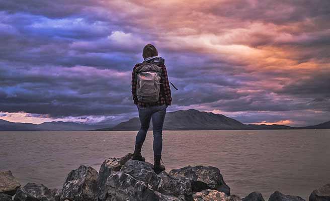 広大な風景の前に立つ女性