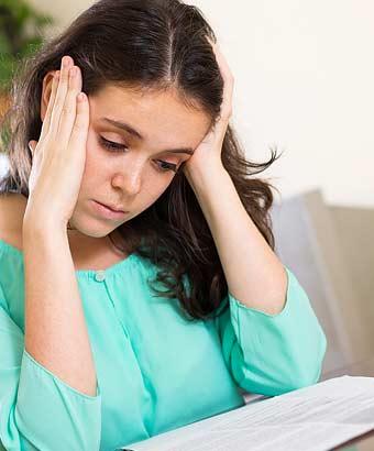 書類を見ながら悲しむ女性
