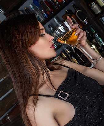 端正な美貌の女性がお酒を飲んでいる