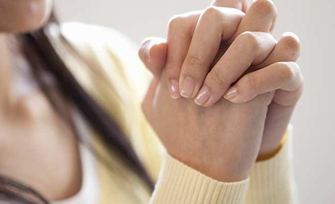 両手を握って祈る女性