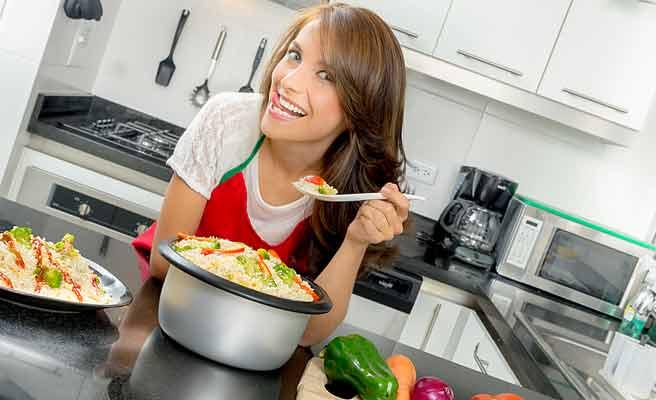台所で料理の味見をする女性