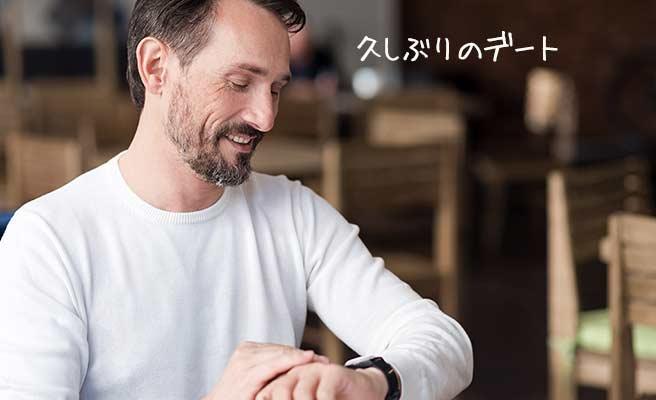腕時計ををみつつ「久しぶりのデート」と思ってる笑顔の男性