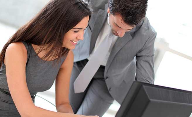パソコンを操作する女性をサポートする男性