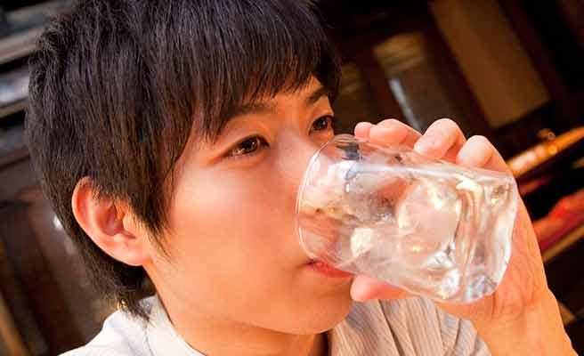グラスで酒を飲み干す男性