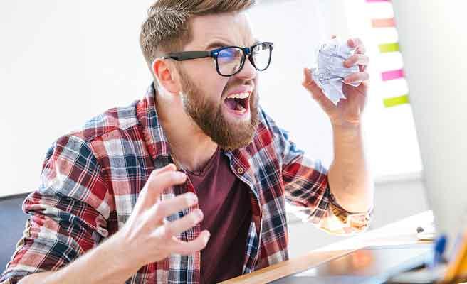 パソコン画面に向かって怒りをぶつける男性