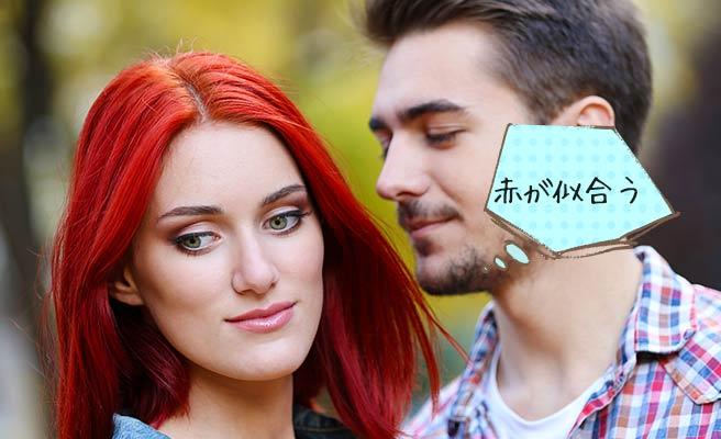 赤い髪の女性の耳元で「似合うと」囁く男性