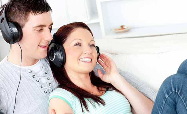 部屋で一緒に音楽を聴くカップル