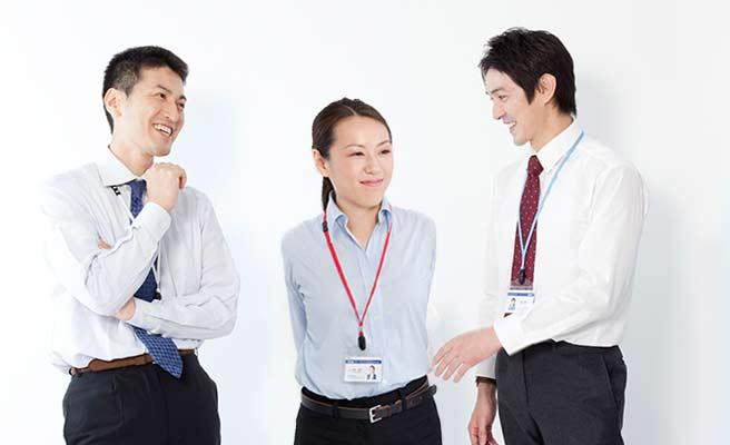 会社で同僚と話す女性
