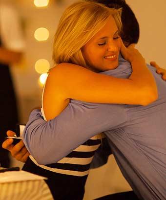 指輪を持つ男性を抱きしめる女性