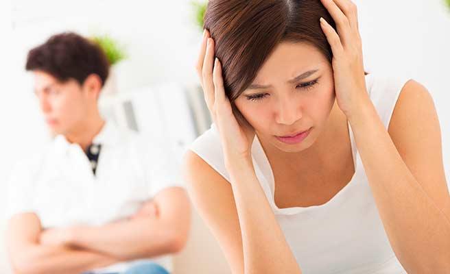 彼氏の傍で頭を抱える女性