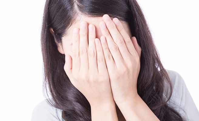 両手で顔を覆う女性
