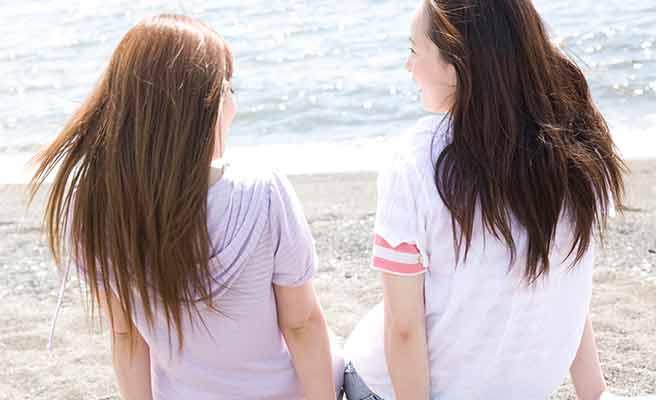 海辺で友達と語る女性