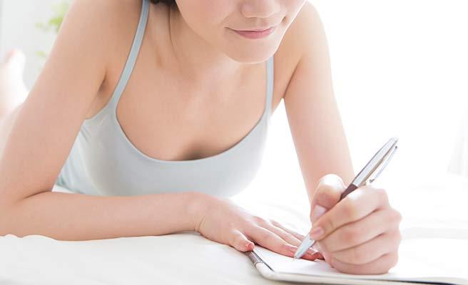 紙に書き込む女性