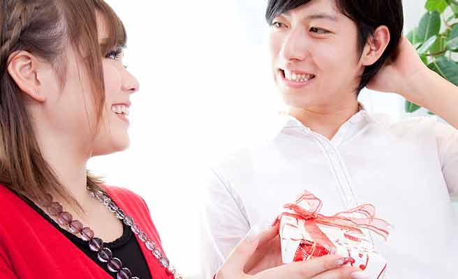 プレゼント送る彼氏に笑顔を向ける女性