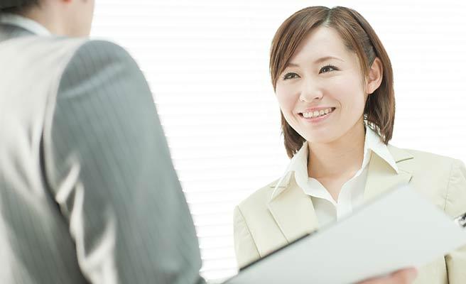 男性の同僚と立ち話する女性