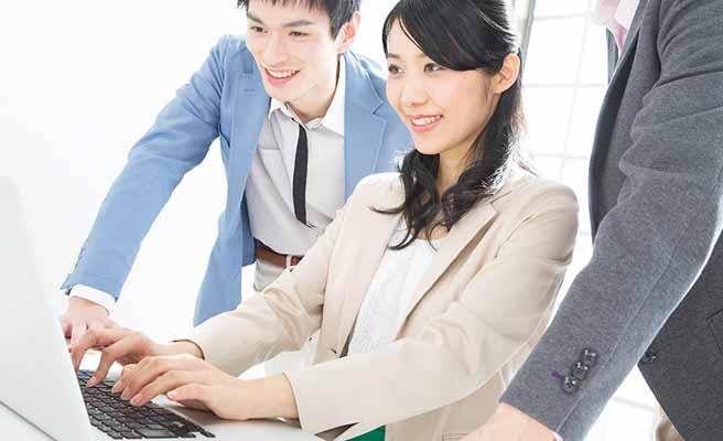 パソコンに向かい作業する女性と見守る同僚男性