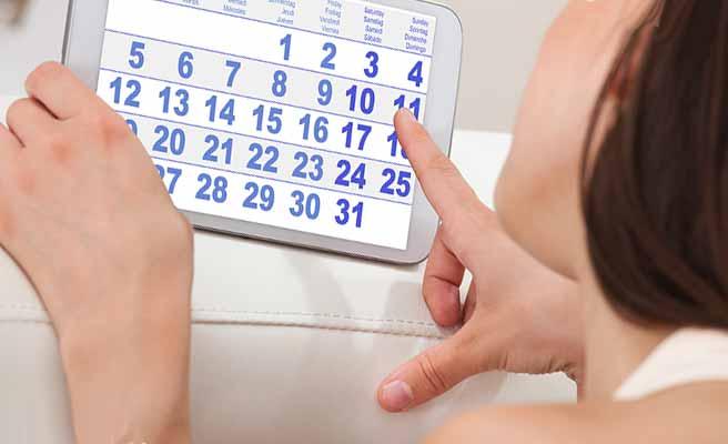 タブレットのカレンダーを指さす女性