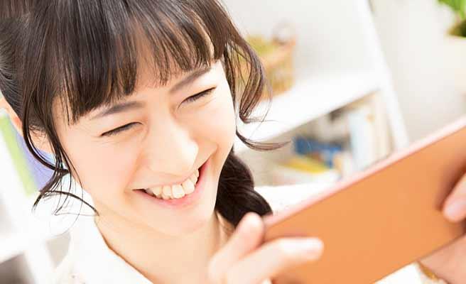 スマホを見て笑顔の女性