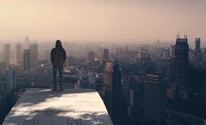 都会のビル群を見つめる男性