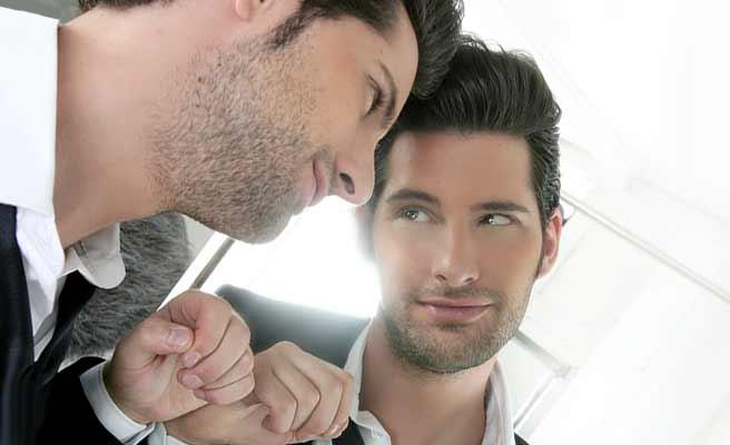 鏡に向かって自分を見つめる男性
