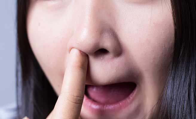 鼻の穴に指を入れる女性