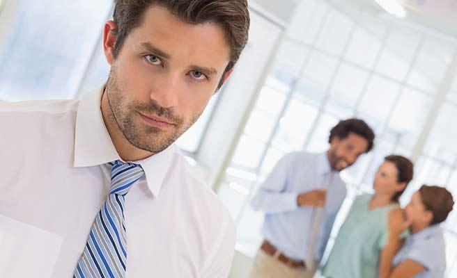 同僚のグループから離れて立つ男性
