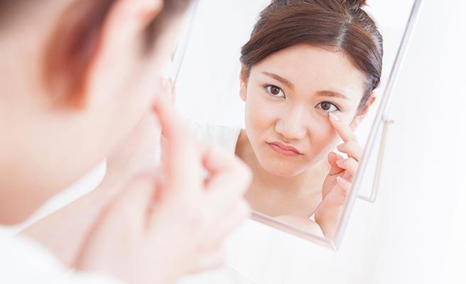 鏡に向かってアイシャドーを確認する女性