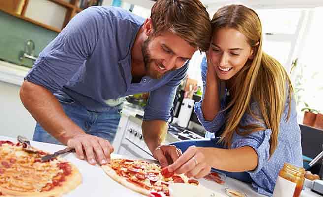 一緒にピザを調理する男女