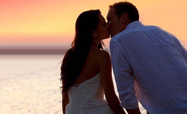 夕日を背景にキスするカップル