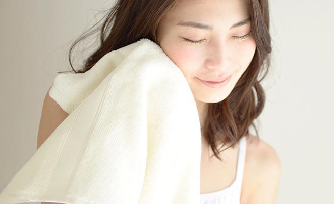 タオルで顔を押さえる女性