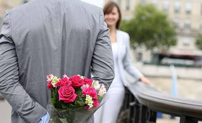 花束を背中に隠して彼女の方に歩み寄る男性