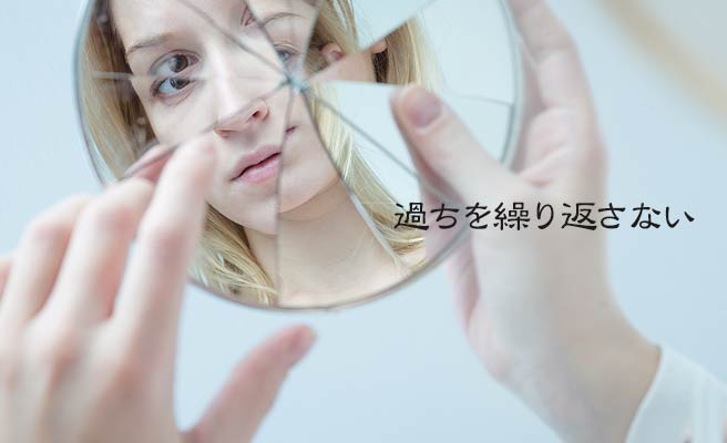 割れた鏡をみる女性