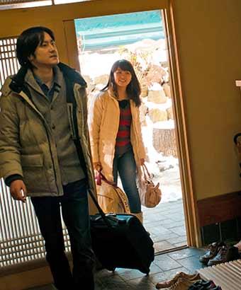 玄関で挨拶するカップル