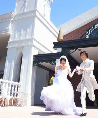 チャペルの前を走る結婚衣装の男女