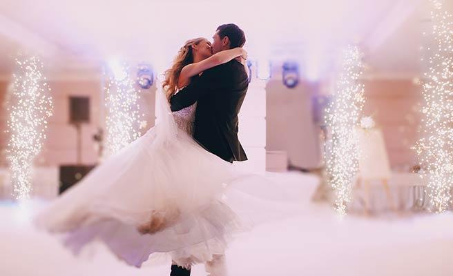 イルミネーションの飾りを背景に踊る新郎新婦