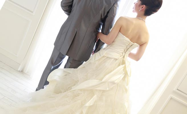 ドレスとタキシード衣裳の男女が腕を組んで立つ