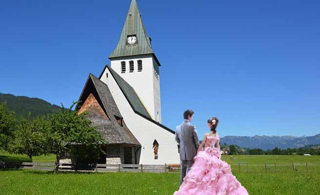 草原の中の教会の前に立つ新郎新婦