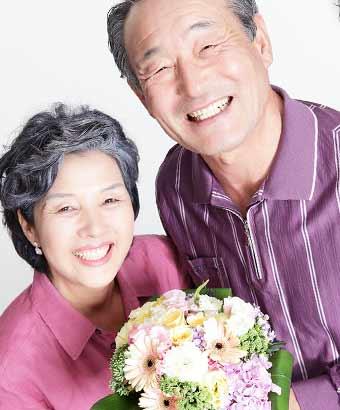 花束を持って笑顔の初老夫婦