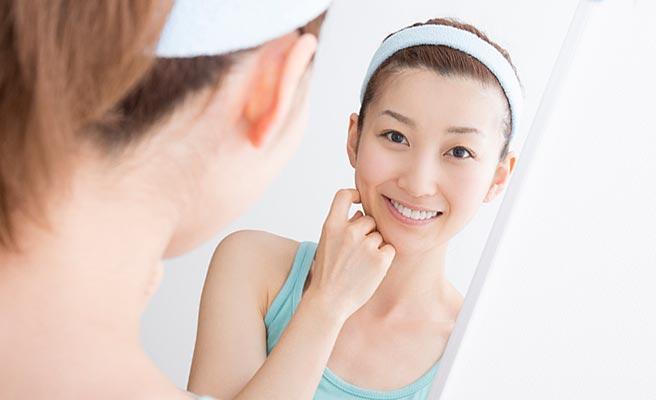 鏡に向かって肌の手入れをする女性