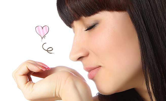 手首に付けた香水の匂いを嗅ぐ女性