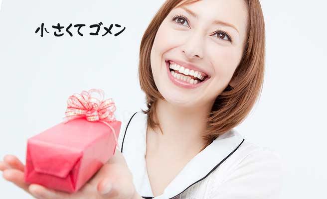 小さなプレゼント箱を差し出す女性