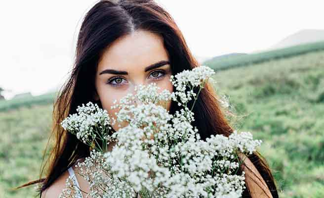 野草の花束で顔を隠して微笑む女性