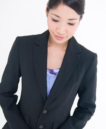 お辞儀をするスーツ姿の女性
